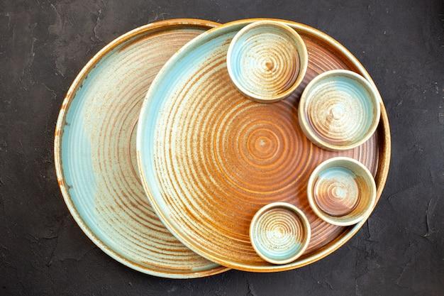 Vista dall'alto piatti marroni con piccoli piatti su superficie scura
