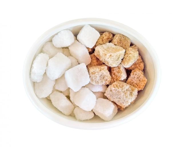 Vista dall'alto di cubetti di zucchero marrone e bianco nella ciotola isolata