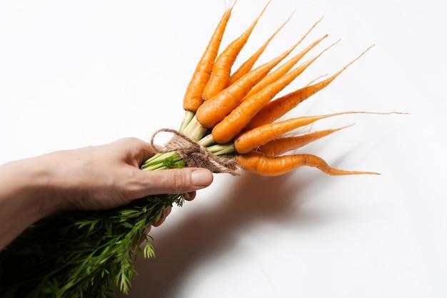 Vista dall'alto del mazzo di carote fresche in mano maschile, su sfondo bianco.