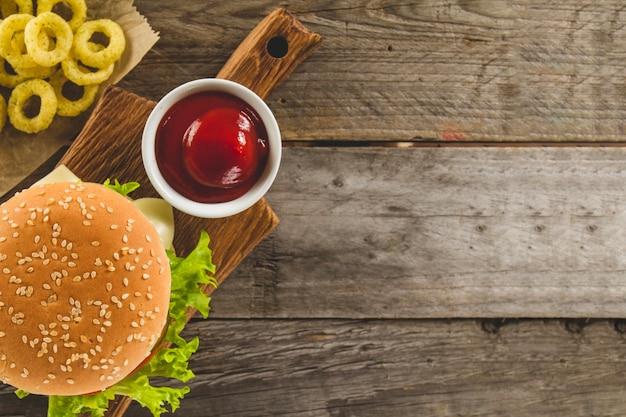 Vista dall'alto di hamburger con anelli di cipolla e salsa di pomodoro