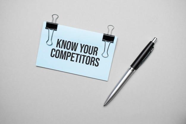 Vista dall'alto di un biglietto da visita con testo conosci i tuoi concorrenti, penna, graffette su una superficie colorata