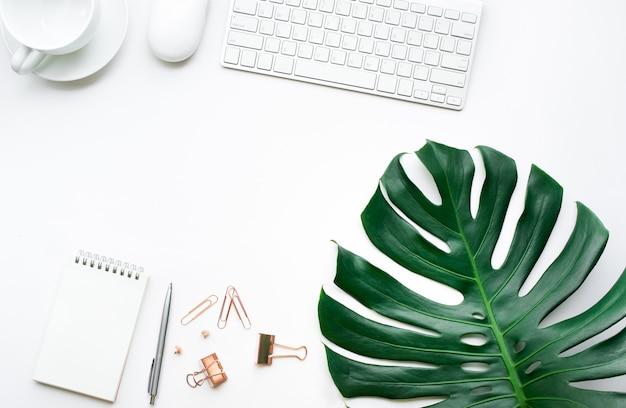 Vista dall'alto del tavolo scrivania da lavoro con foglie di monstera e mock up accessori su sfondo bianco.design piatto.spazio copia