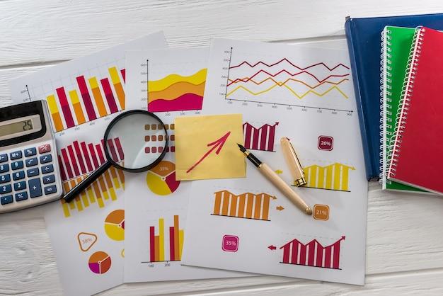 Vista dall'alto di grafici aziendali con lente d'ingrandimento, penna e calcolatrice