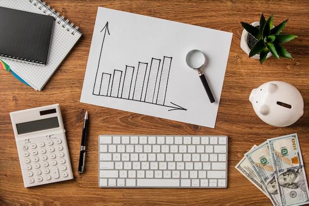 Vista dall'alto di oggetti aziendali e grafico di crescita con lente d'ingrandimento