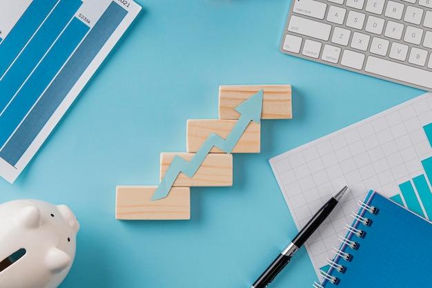 Vista dall'alto di oggetti aziendali con freccia di crescita su blocchi di legno e salvadanaio Foto Premium