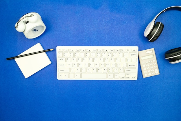 Vista dall'alto di oggetti aziendali tastiera, mouse, cuffie, scartoffie con matita e sveglia su sfondo di carta blu lay minimo piatto copia spazio per sfondo aziendale e sito web.