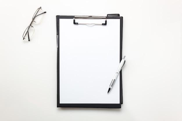 Vista dall'alto scrivania aziendale scrivania, carta appunti, occhiali da vista sulla scrivania bianca con spazio di copia.
