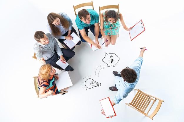 Vista dall'alto di uomini d'affari in una riunione su sfondo bianco. tutti seduti con blocco note e penna. oratore in piedi e allargando le braccia