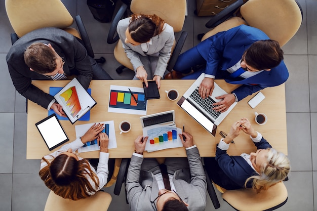 Vista dall'alto di uomini d'affari seduti in sala riunioni e lavorando su un progetto importante per un grande cliente.