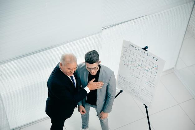 Vista dall'alto. uomo d'affari congratulandosi con un dipendente su una presentazione di successo