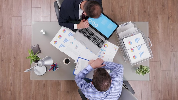 Vista dall'alto dell'uomo d'affari che spiega i grafici aziendali ai partner utilizzando il laptop mentre discutono le statistiche finanziarie durante la partnership commerciale. imprenditore che lavora presso la gestione degli investimenti in ufficio