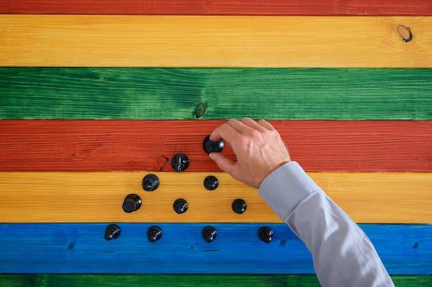 Vista dall'alto della mano dell'uomo d'affari che fa una forma di piramidi di figure di scacchi nere su uno sfondo di legno colorato.
