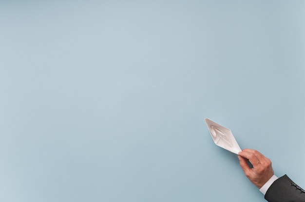 Vista superiore dell'uomo d'affari che tiene la carta fatta barca di origami sull'azzurro