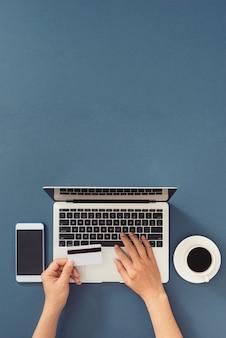 Vista dall'alto della scrivania dell'ufficio dell'uomo d'affari con carta di credito per il pagamento online sul computer portatile