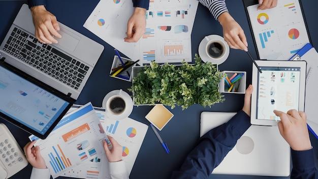 Vista dall'alto dell'uomo d'affari che mostra le statistiche di gestione dell'azienda utilizzando la tavoletta digitale