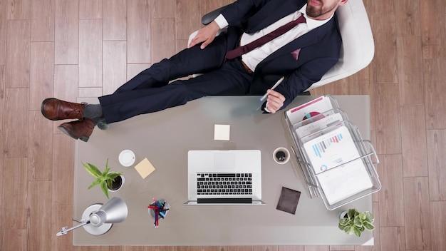 Vista dall'alto dell'uomo d'affari in tuta che si rilassa con i piedi sulla scrivania dell'ufficio