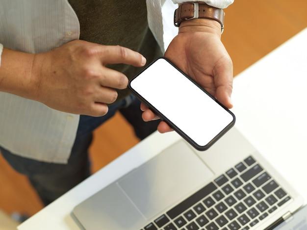 Vista dall'alto dell'uomo d'affari utilizza lo smartphone con lo schermo mentre si trovava nell'area di lavoro