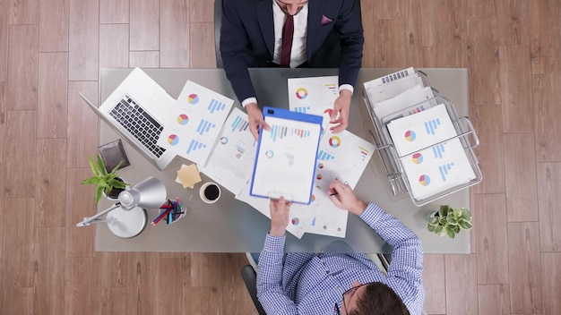 Vista dall'alto di uomini d'affari che condividono documenti aziendali analizzando il profitto finanziario