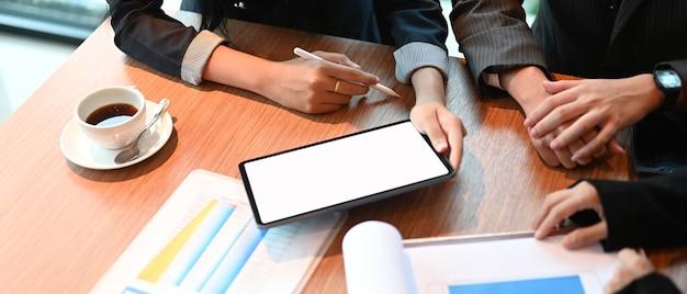 Vista dall'alto di uomini d'affari che lavorano insieme con tablet mockup e grafico finanziario