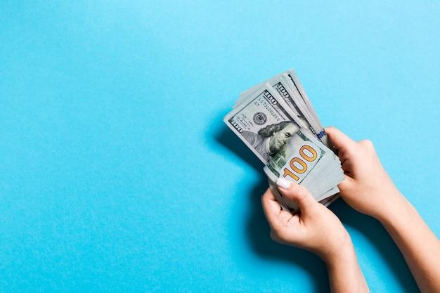 Vista dall'alto delle mani di una donna d'affari contando un centinaio di banconote in dollari su sfondo colorato. concetto di successo e ricchezza con spazio di copia