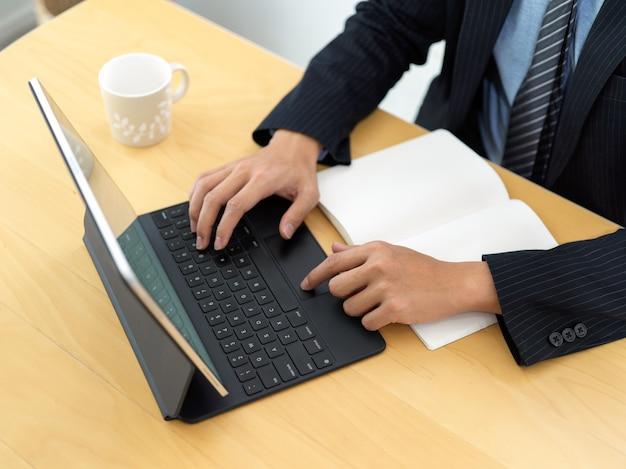 Vista superiore della donna di affari che digita sulla tastiera della compressa sulla tavola di legno con il taccuino in bianco