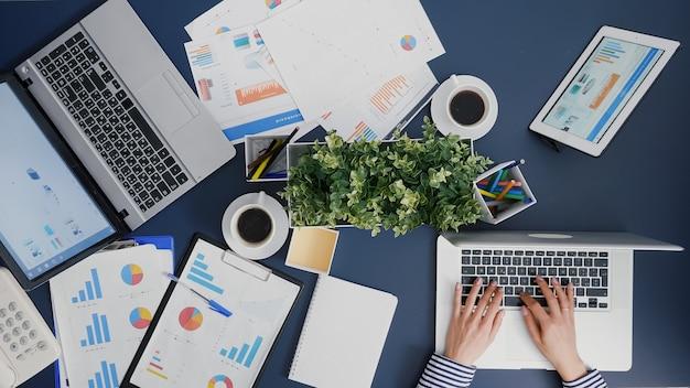 Vista dall'alto della donna d'affari che lavora ai grafici della società finanziaria sul computer