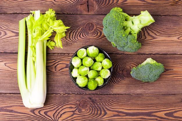 Vista dall'alto su cavoli, broccoli, cavolini di bruxelles e sedano - ingredienti per piatti vegetariani.