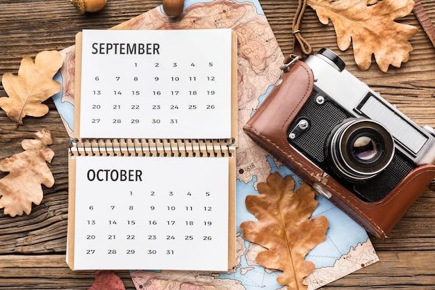 Vista dall'alto del calendario con fotocamera e foglie di autunno