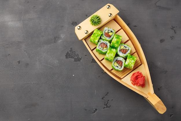 Vista dall'alto del rotolo di sushi della california nella piastra su sfondo nero