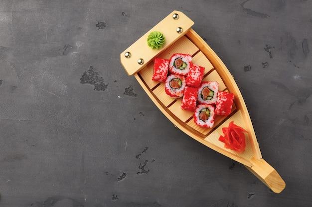 Vista dall'alto del rotolo di sushi della california nel piatto sulla tavola nera
