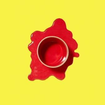 Vista dall'alto sopra può con vernice rossa nel mezzo della pozzanghera versata su uno sfondo giallo con ombre dure, copia spazio.