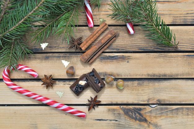 Vista superiore sul cioccolato delle canne di caramella e sulla spezia su di legno nella decorazione di natale
