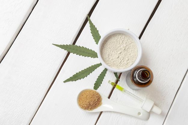 Vista dall'alto di prodotti a base di cannabis marijuana farina zucchero olio om legno bianco sfondo