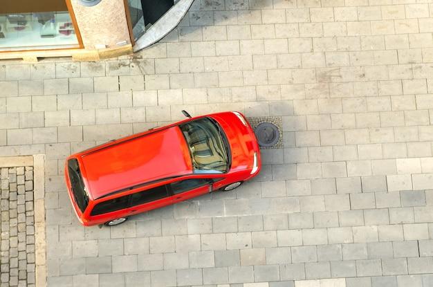 Vista dall'alto di un'auto che guida su una strada cittadina.