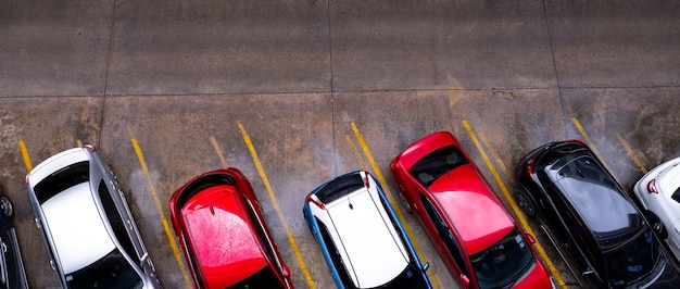 Vista dall'alto della macchina parcheggiata nel parcheggio auto in cemento con la linea gialla del segnale stradale sulla strada.