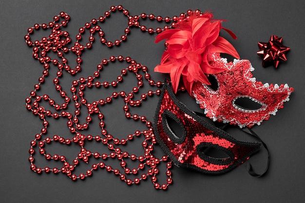 Vista dall'alto di maschere di carnevale con perline e fiocco