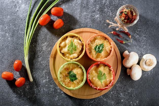 Vista dall'alto della casseruola con formaggio al forno, pollo e funghi in noci di cocco multicolori con verdure su sfondo grigio