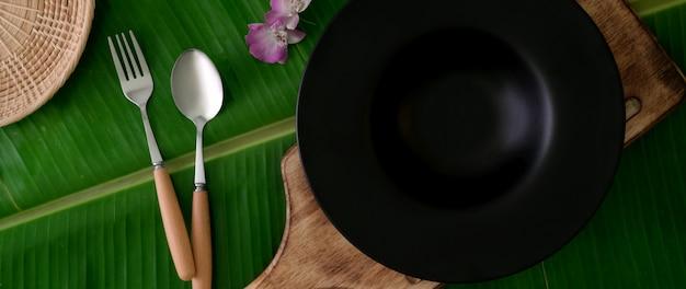 Vista dall'alto del piatto in ceramica sul vassoio in legno con cucchiaio e folk su foglia di banana