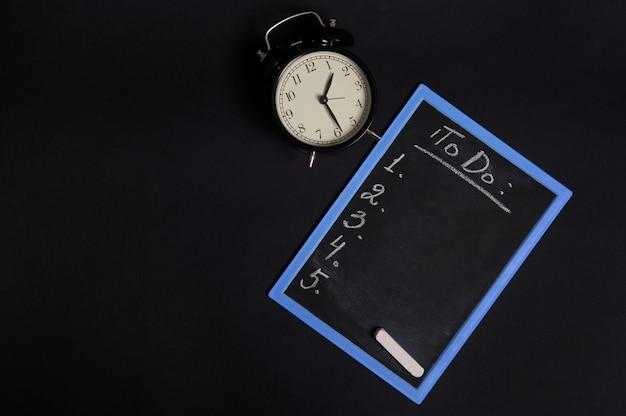 Vista dall'alto di una lavagna con un elenco di lettere da fare, con spazio vuoto per le copie e una sveglia vintage. isolato su sfondo nero. concetti di pianificazione, gestione del tempo, orari e tempistiche.
