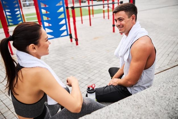 Vista dall'alto di un uomo e una donna atletici allegri con asciugamani che si rilassano e bevono acqua sul campo sportivo