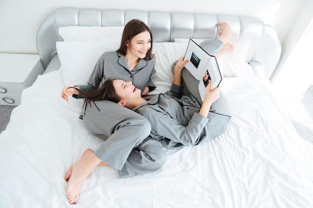 Vista dall'alto di giovani sorelle gemelle allegre e attraenti che leggono un libro e ridono in camera da letto