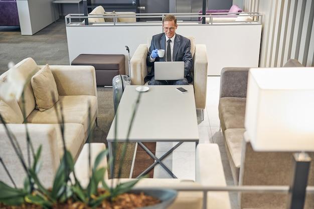 Vista dall'alto di un uomo d'affari allegro ed elegante seduto in aeroporto con guanti di gomma mentre beve caffè e usa il taccuino