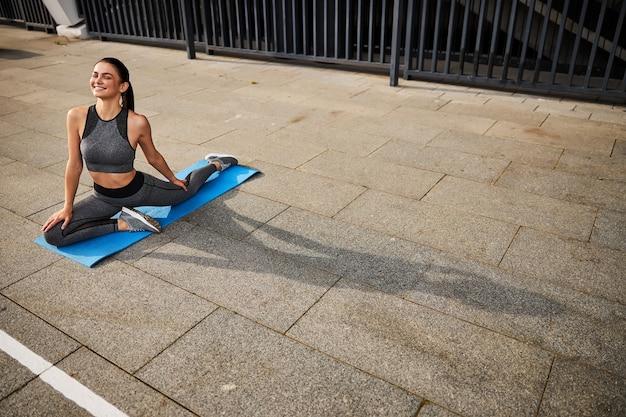 Vista dall'alto di una donna magra allegra in abbigliamento sportivo che fa esercizi di stretching sul tappetino nel centro della città
