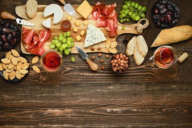 Vista dall'alto del piatto di formaggi con prosciutto, uva, miele, datteri, cracker, noci e vino