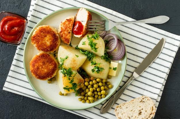 Vista dall'alto di cotolette arrosto impanate di pollo con patate bollite e piselli germinati serviti con cipolla e ketchup.