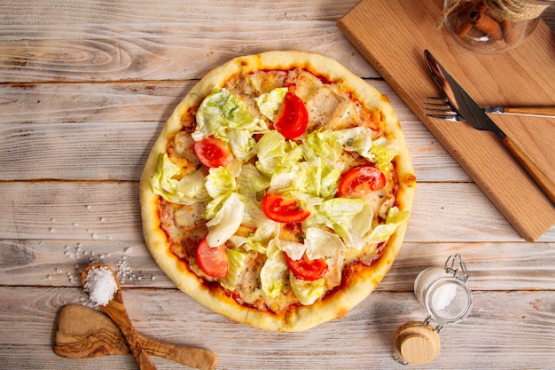 Vista dall'alto sulla pizza caesar di pollo con pomodori e lattuga