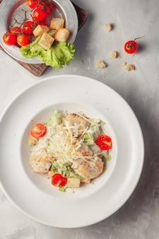 Vista dall'alto di insalata caesar di pollo su sfondo grigio