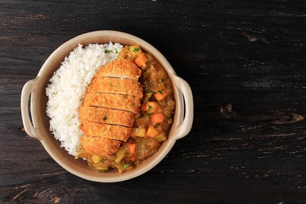 Vista dall'alto cotoletta di pollo al curry con riso - stile alimentare giapponese. vista dall'alto su piatto in ceramica tavolo in legno nero con dadi di patate e carote, spazio per copiare il testo