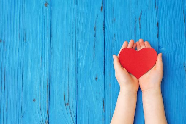 Vista dall'alto il bambino tiene in mano un cuore rosso su sfondo blu in legno. spazio vuoto per il testo. amore del bambino, donazione, concetto medico.