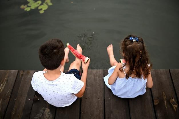 Vista dall'alto dei bambini sulla cuccetta con i piedi abbassati nel lago, mangiando anguria all'aperto. concetto di vacanze estive di campagna.